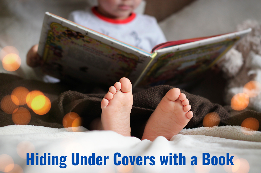 Hiding under covers with a book